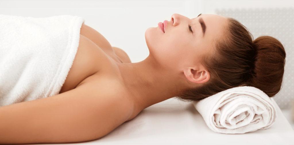 Frau liegt auf der Massageliege im Wellness